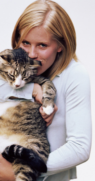 blonde woman holding her tabby cat